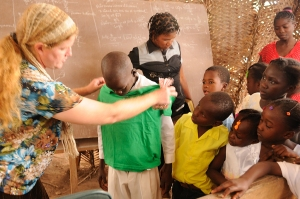 Missionary, Laura , handing out clothes to children after Sunday service.